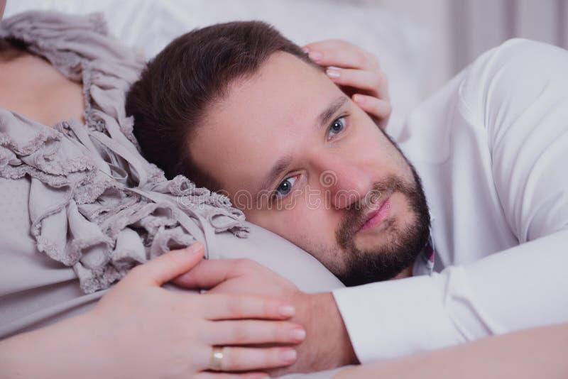 Marido que escuta a barriga da sua esposa imagem de stock royalty free