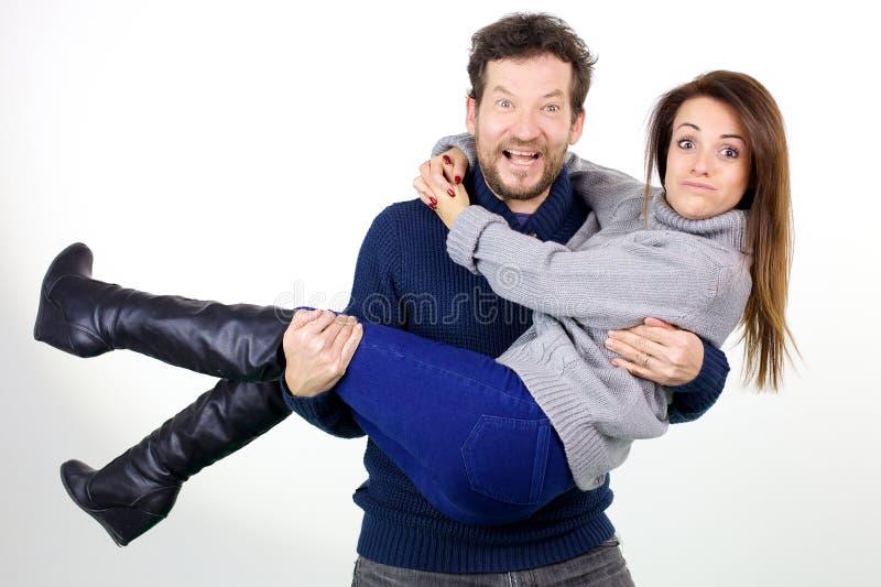 Marido que hace la cara divertida mientras que se sostiene en esposa linda del pelirrojo de los brazos imágenes de archivo libres de regalías