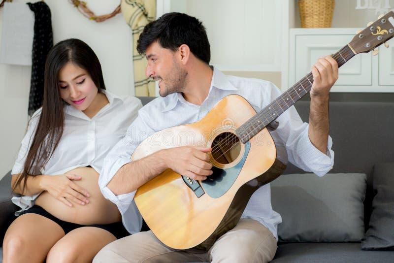 Marido que juega la guitarra y a la mamá embarazada hermosa en la sala de estar en el sofá foto de archivo