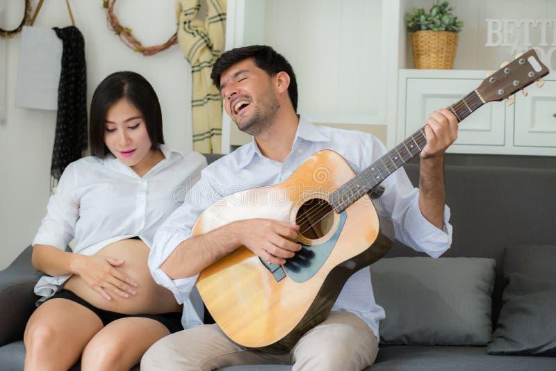 Marido que juega la guitarra y a la mamá embarazada hermosa en la sala de estar en el sofá imagenes de archivo