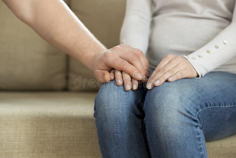 Marido que lleva a cabo la mano de su esposa, dando la ayuda emocional Ment fotos de archivo libres de regalías