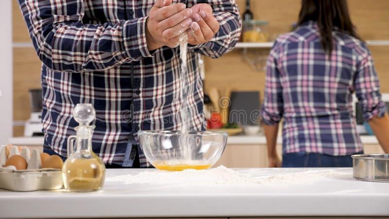 Marido que tem o divertimento com farinha quando sua esposa olhar afastado foto de stock