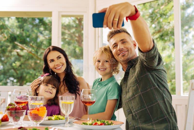 Marido que toma su smartphone mientras que hace el selfie con la familia foto de archivo