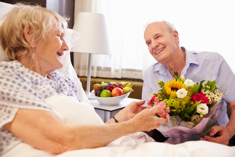 Marido que visita a la esposa mayor en hospital con las flores fotos de archivo