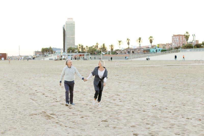 Marido superior e esposa felizes que correm na praia da areia e que guardam as mãos fotografia de stock royalty free