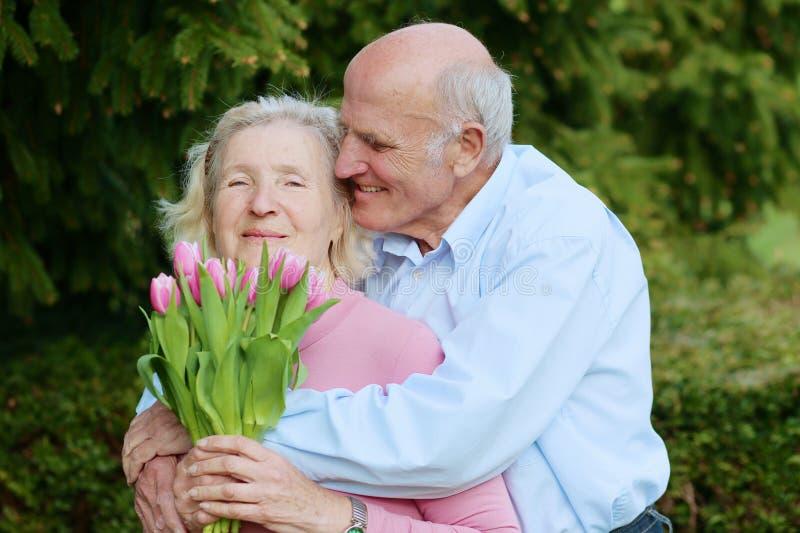 Marido superior que dá o ramalhete das tulipas a sua esposa foto de stock