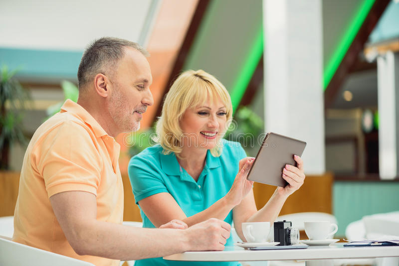 Marido y esposa alegres que usa tecnología moderna fotografía de archivo