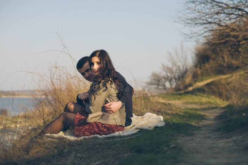 Marido y esposa en la orilla del lago con las orillas rocosas, primavera temprana Siluetas de los amantes que entran el agua en l imagen de archivo