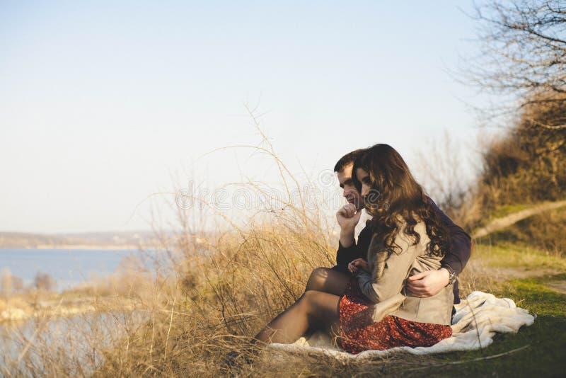 Marido y esposa en la orilla del lago con las orillas rocosas, primavera temprana Siluetas de los amantes que entran el agua en l imagenes de archivo