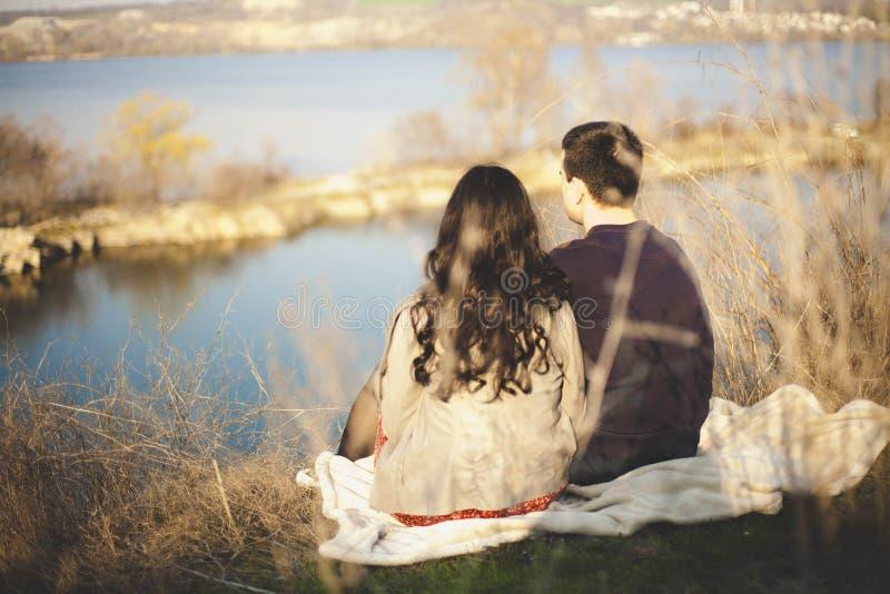 Marido y esposa en la orilla del lago con las orillas rocosas, primavera temprana Siluetas de los amantes que entran el agua en l foto de archivo libre de regalías