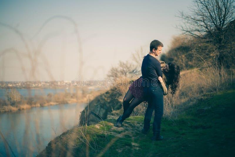 Marido y esposa en la orilla del lago con las orillas rocosas, primavera temprana Siluetas de los amantes que entran el agua en l fotografía de archivo libre de regalías