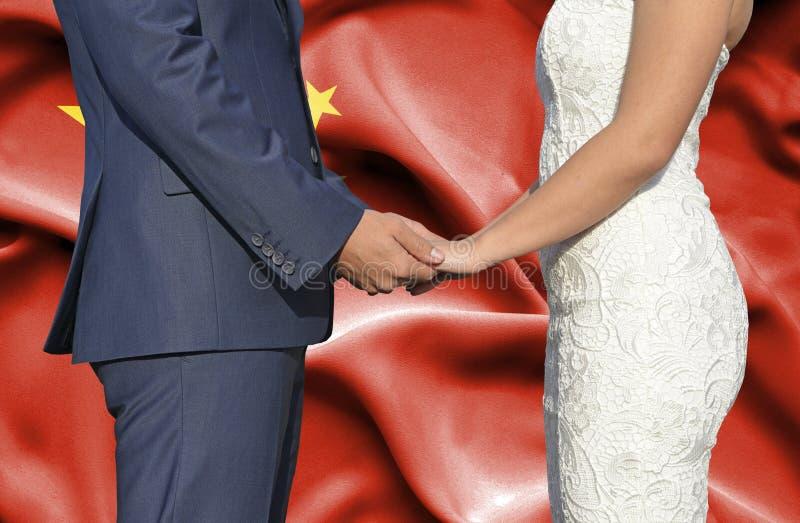 Marido y esposa que llevan a cabo las manos - fotograf?a conceptual del matrimonio en China foto de archivo