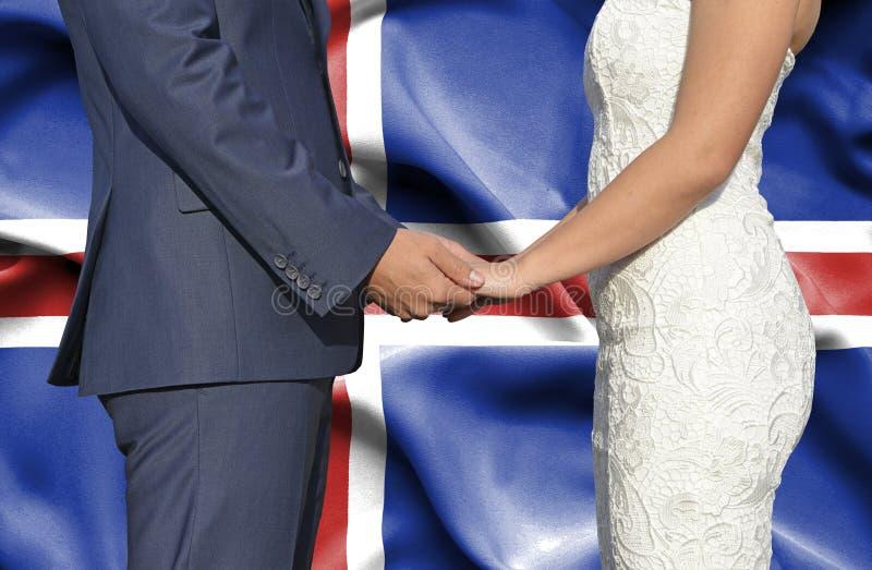 Marido y esposa que llevan a cabo las manos - fotograf?a conceptual del matrimonio en Islandia imagen de archivo