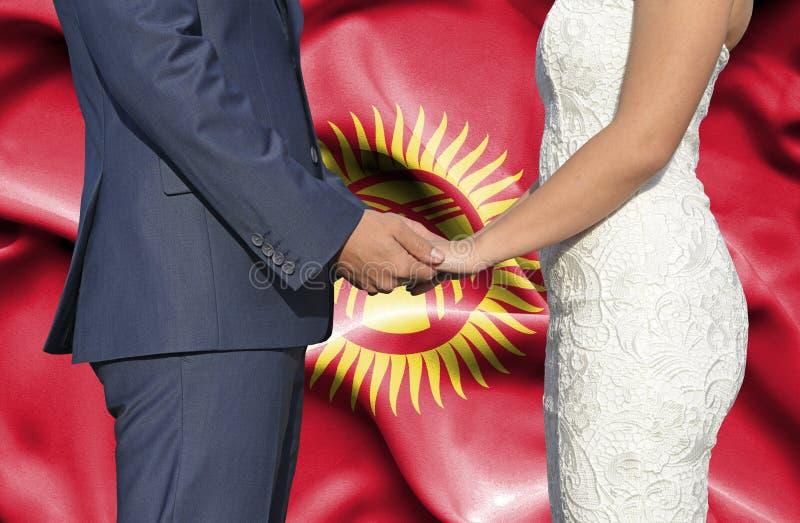 Marido y esposa que llevan a cabo las manos - fotograf?a conceptual del matrimonio en Krygyzstan foto de archivo libre de regalías