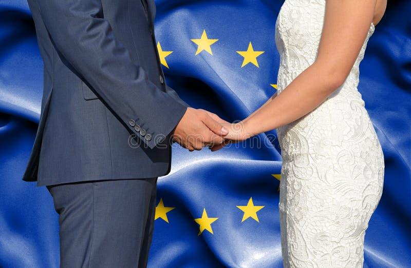 Marido y esposa que llevan a cabo las manos - fotograf?a conceptual del matrimonio en la uni?n europea foto de archivo