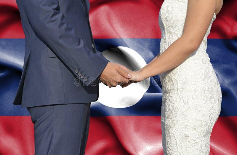 Marido y esposa que llevan a cabo las manos - fotograf?a conceptual del matrimonio en Laos imagen de archivo libre de regalías