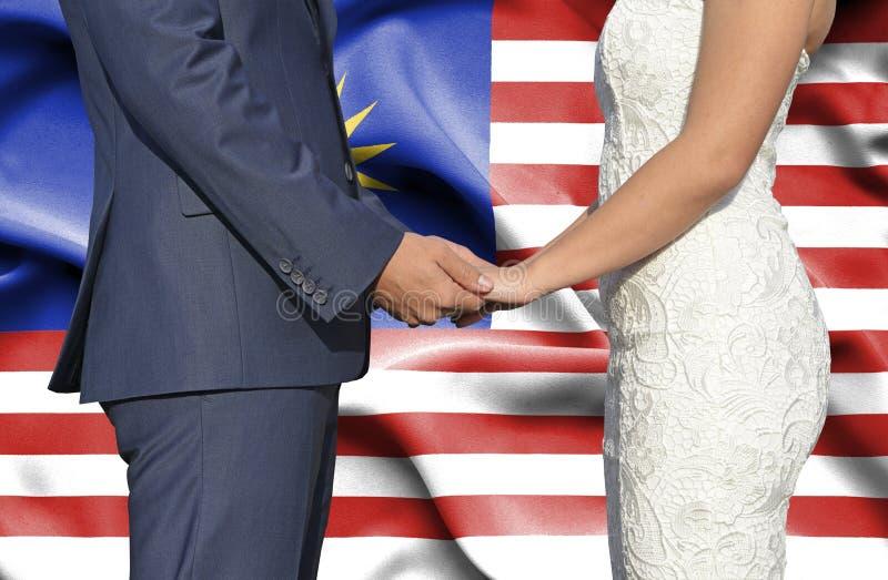 Marido y esposa que llevan a cabo las manos - fotograf?a conceptual del matrimonio en Malasia imagenes de archivo