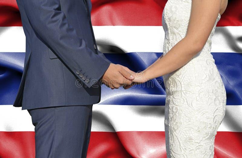 Marido y esposa que llevan a cabo las manos - fotograf?a conceptual del matrimonio en Tailandia imagenes de archivo