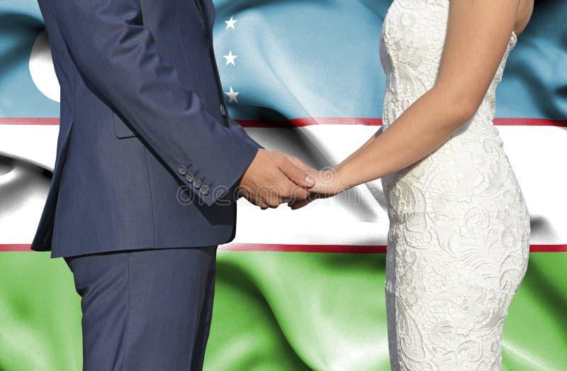 Marido y esposa que llevan a cabo las manos - fotograf?a conceptual del matrimonio en Uzbekist?n imagen de archivo libre de regalías