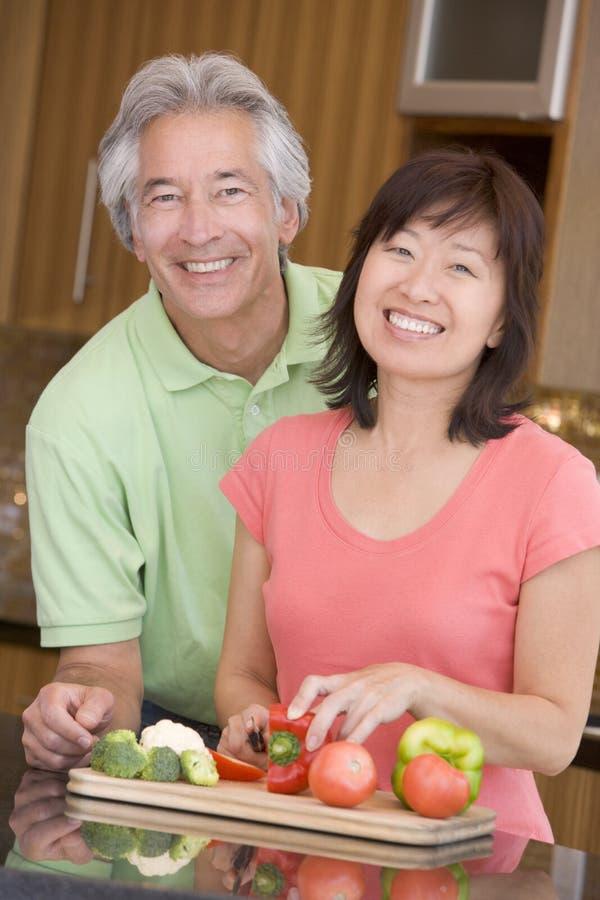 Marido y esposa que preparan la comida, mealtime junto fotografía de archivo libre de regalías