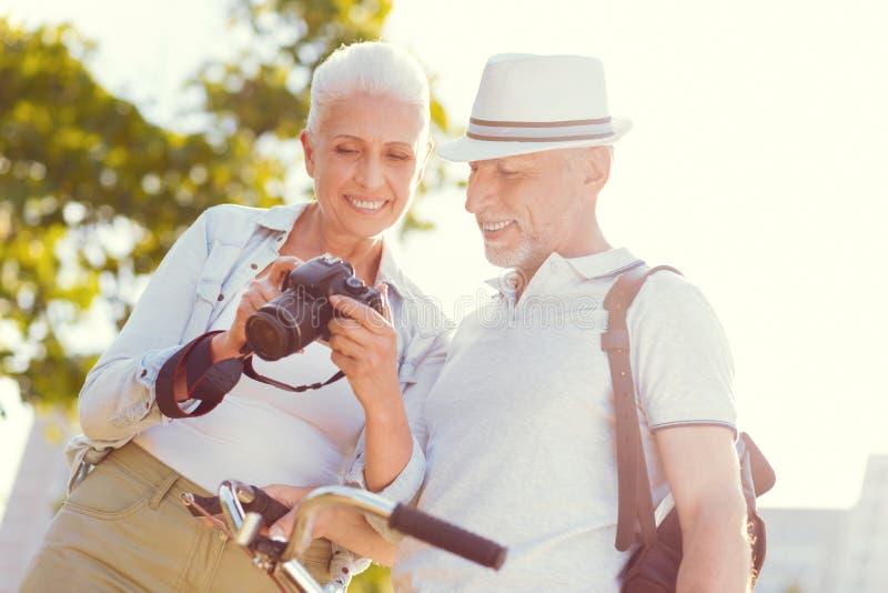 Marido y esposa sonrientes que gozan de las fotos de familia al aire libre imagen de archivo libre de regalías