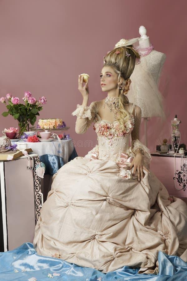 Marie Antoinette dans le rose tenant un petit gâteau photo stock