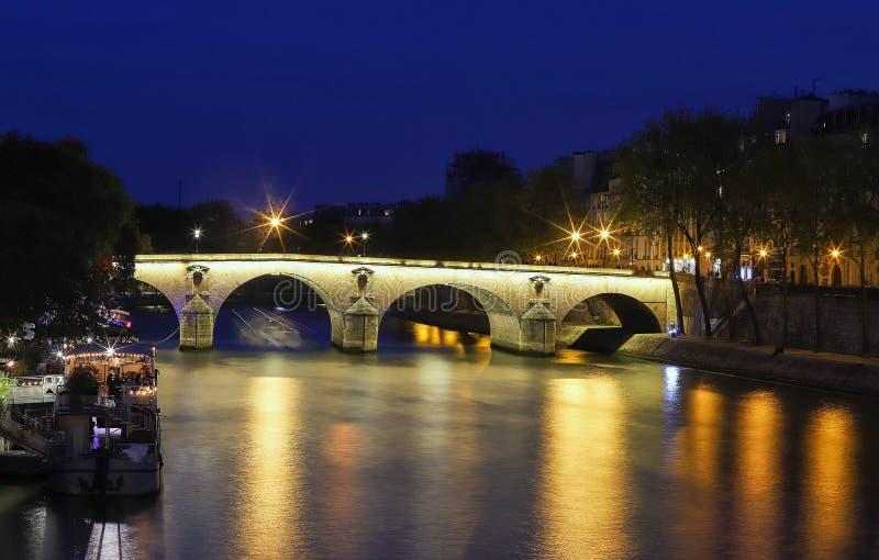 Marie Bridge mellan helgonet Louis Island och den Quai desen Celestins Sikt från floden Seine på natten, Paris arkivbild