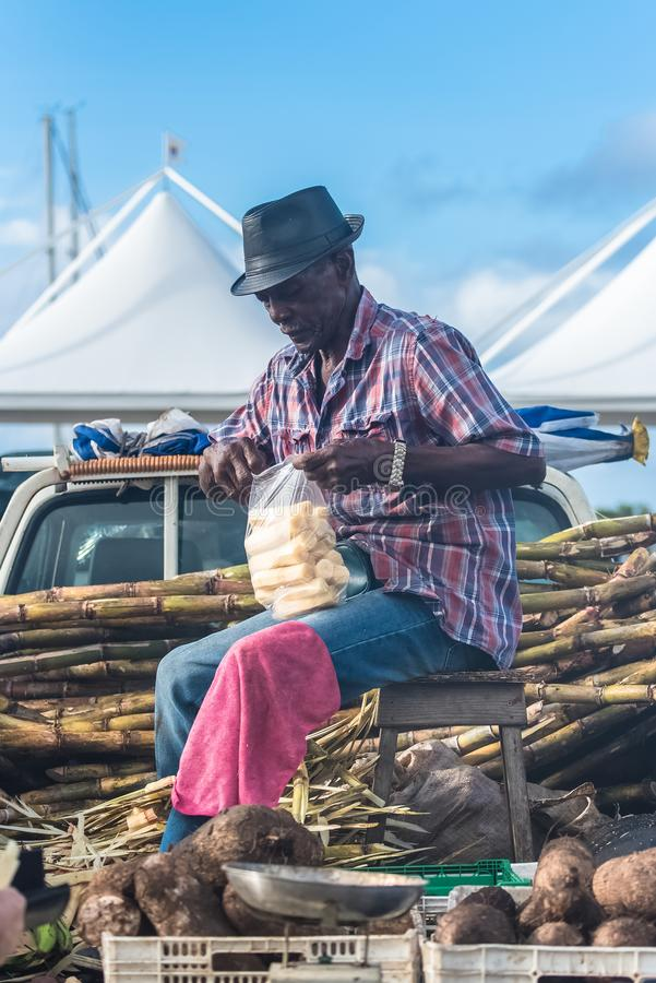 Marie-Galante island in Guadeloupe. January 13th, 2018, man who peels some sugar cane on the market stock photos