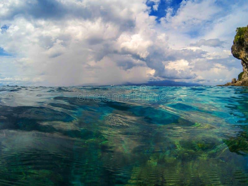 Marien landschap met transparant water en blauwe hemel Het blauwe zeewater ziet door eruit stock fotografie