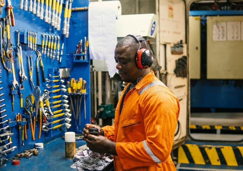 Mariene werktuigkundige die in motorruimte werken stock afbeelding