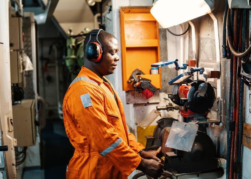 Mariene werktuigkundige die in motorruimte werken stock afbeeldingen