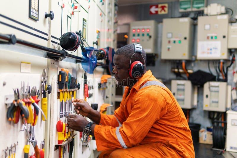Mariene werktuigkundige die in motorruimte werken stock foto's