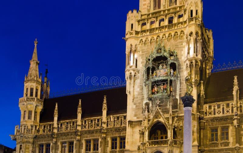 Marienplatz glockenspiel på skymning i Munich fotografering för bildbyråer