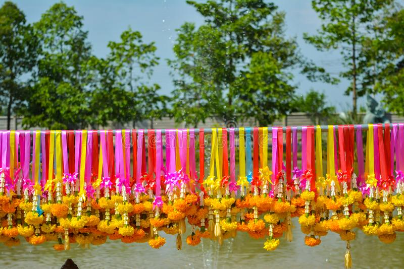 Marigold η γιρλάντα λουλουδιών κρεμά στις ζωηρόχρωμες ράγες στοκ φωτογραφίες
