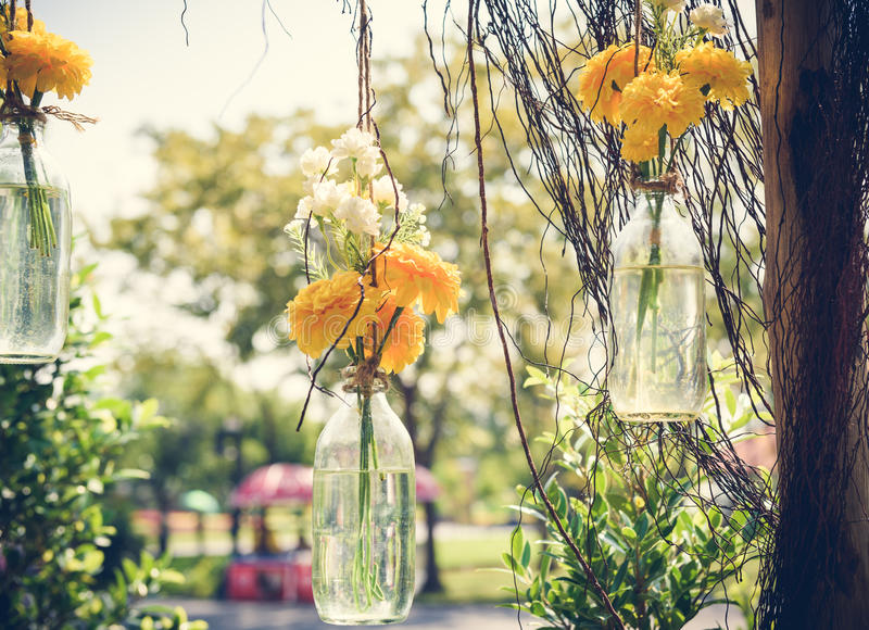 The marigold flowers in a glass bottle hanging. Flower vase arrangements stock photography