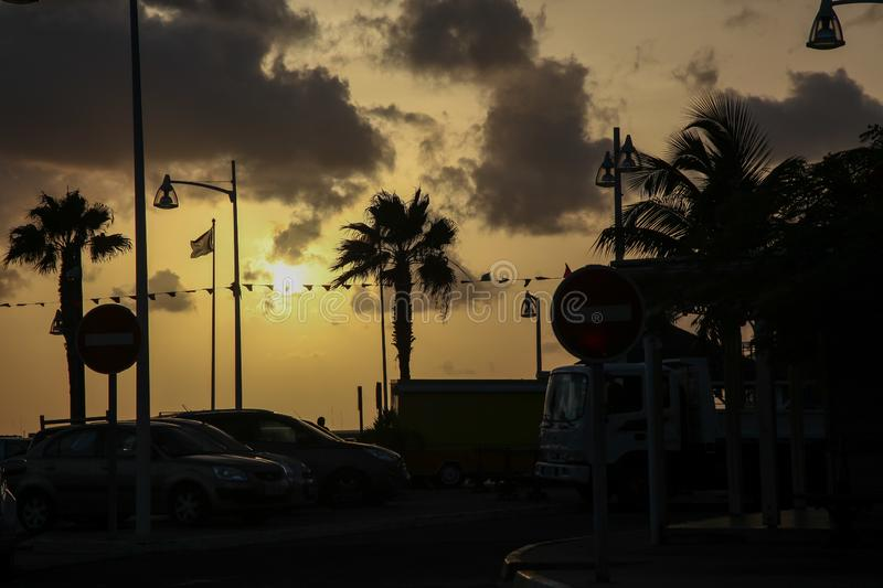 Beautifull sunset with palm trees and cars silhuetes stock image