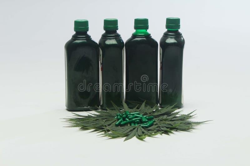 Marihuana liść z zielonymi pastylkami i cztery butelką zdjęcia royalty free