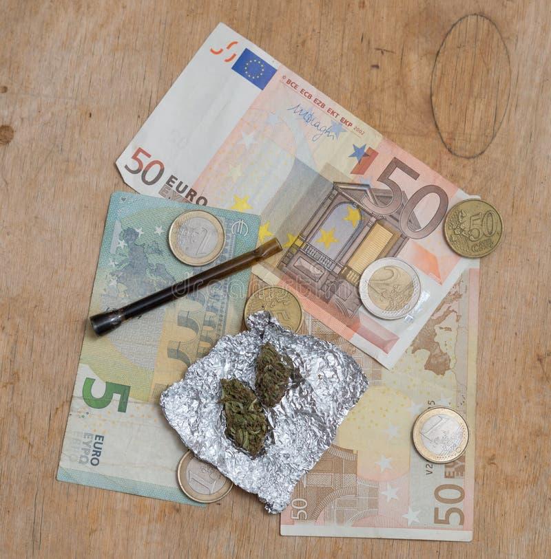 Marihuana in tinfolie met pijp en Euro geldachtergrond stock fotografie