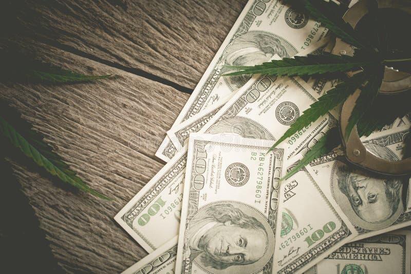 Marihuanablad met dollars en ijzerhandcuffs royalty-vrije stock afbeeldingen