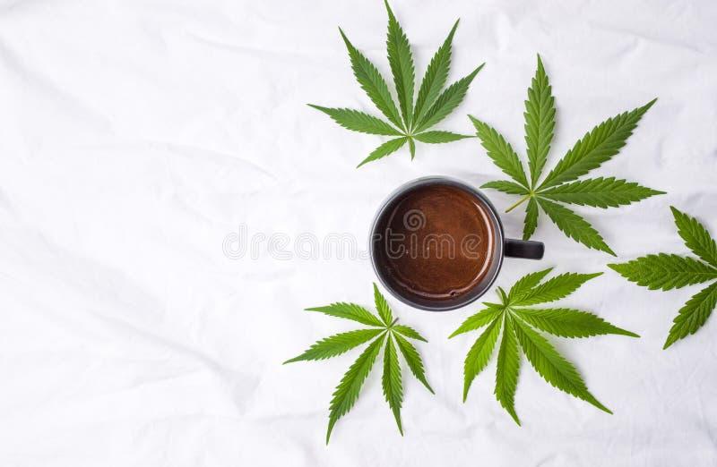 Marihuanabladeren en een kop van koffie stock afbeelding