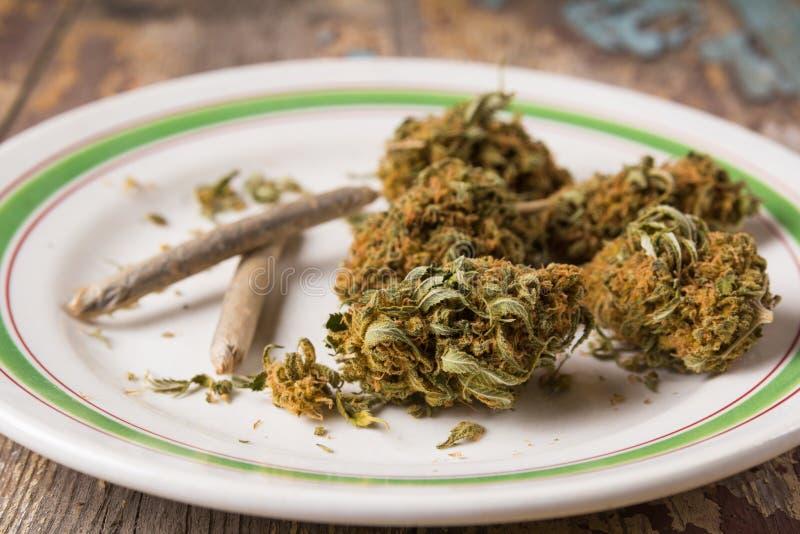 Marihuanaknoppen en verbindingen in de witte plaat stock afbeelding