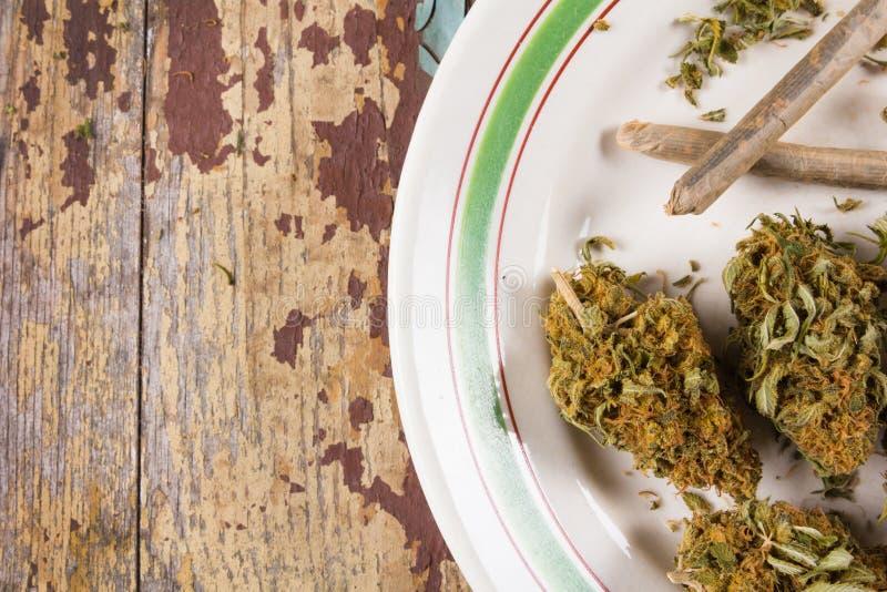 Marihuanaknoppen en verbindingen in de witte plaat stock foto
