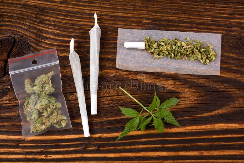 Marijuana background. Cannabis joint, bud in plastic bag and hemp leaves on wooden table. Addictive drug or alternative medicine stock image