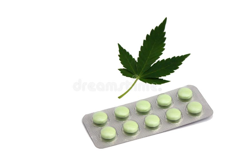 Marijuana cannabis medicine drug cure remedy medicament pills. Green tables and ganja leaf isolated on white royalty free stock photo