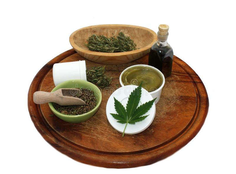 Marijuana products, cannabis tincture, dry weed buds, seeds, hemp salve on wooden desk isolated on white royalty free stock photography