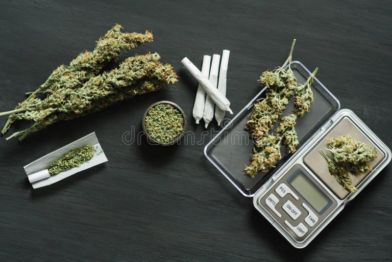 Marijuana, vågen, sidoposter och en cannabismolar rensar på en svart träbästa sikt för tabellöverkant fotografering för bildbyråer