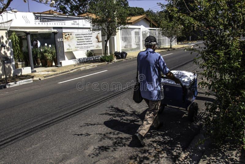 Ice cream hawker walks down a street of Marilia city. Marilia, Sao Paulo, Brazil, September 09, 2019: Ice cream hawker walks down a street of Marilia city stock photography