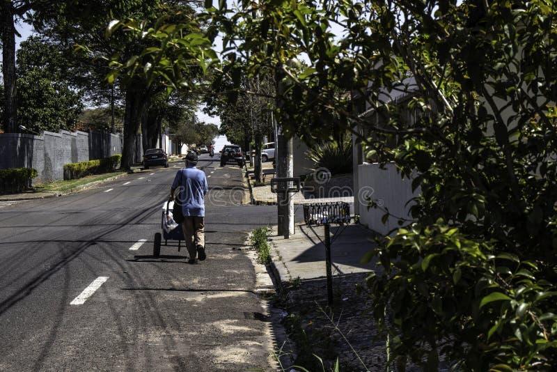 Ice cream hawker walks down a street of Marilia city. Marilia, Sao Paulo, Brazil, September 09, 2019: Ice cream hawker walks down a street of Marilia city stock images