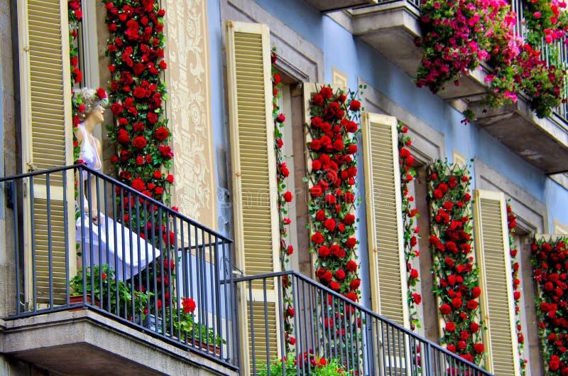 Marilin skyltdocka på en balkong av en byggnad, var fasaden täckas med röda rosor, Barcelona Spanien royaltyfria foton