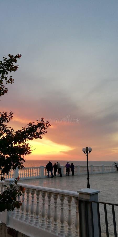 Marin- aftonsolnedgånglandskap i röda, rosa, blåa purpurfärgade färger Folket ser solnedgång nära den vita balustradstranden royaltyfri fotografi